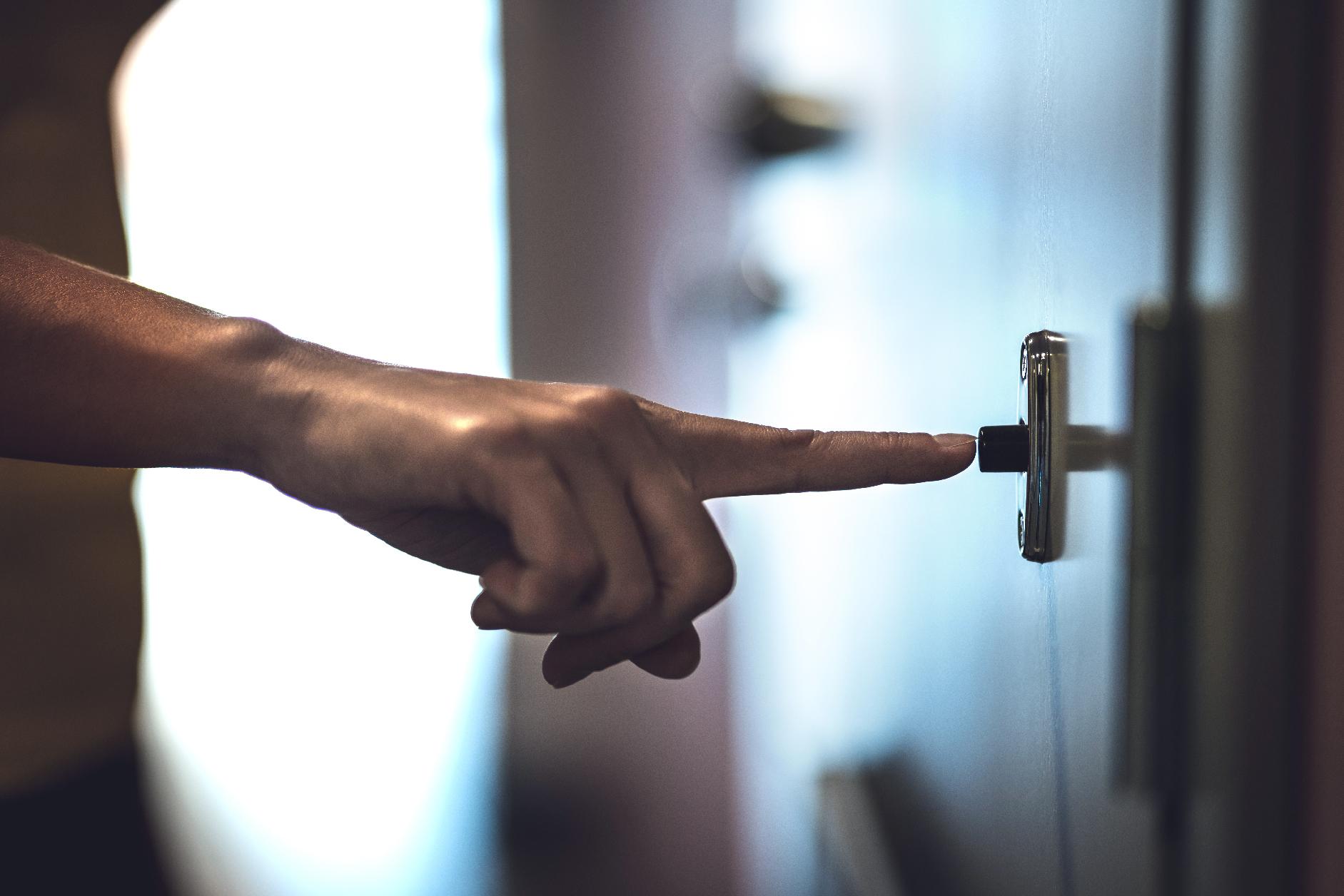 Hand ringing doorbell